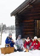 Family taking a break by a mountain hut, Sweden.