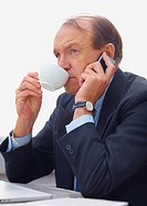 A serious senior business man talking a phone while drinking tea