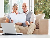 Senior man and woman with laptop reading documents at their house