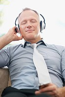 Smart mature business man enjoying pleasant music on an mp3 player