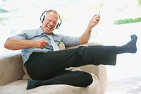 Happy energetic middle aged business man enjoying music on the headphones