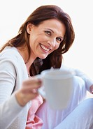 Portrait of a pretty cheerful middle aged woman offering you a cup of coffee