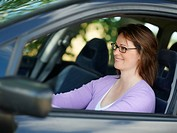 Portrait of a smiling young woman driving a car