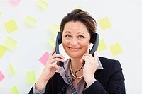 Pretty mature business woman speaking on two phones at the same time