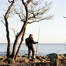 Man fishing by the sea, Sweden.