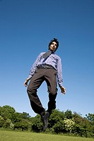 Man in shirt, tie and trousers jumping in park