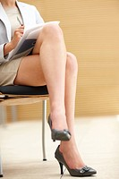 Low section image of legs of a business woman working in her office