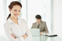 Smiling confident business woman with hands folded and colleague at the back