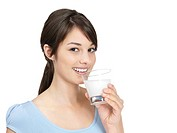 Portrait of a cute young female drinking a glass of milk isolated against white
