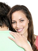 Portrait of a cute young female hugging a man against white background