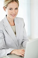 Smiling young business woman working on a laptop