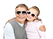 Portrait of a happy old man with her granddaughter wearing goggles on white background
