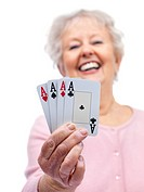 Happy senior woman holding playing cards with all four aces on white background