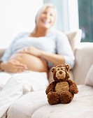 Smiling middle aged pregnant lady sitting on couch with teddy bear