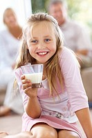 Closeup portrait of adorable small girl holding a glass of milk while her parents sitting in background at home