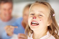Closeup portrait of funny young girl having jam on her nose with parents having breakfast at back