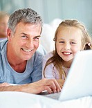 Portrait of happy father and cute daughter using laptop at home