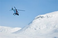 A helicopter flying above mountains covered in snow, Sweden.