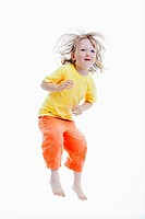 energetic boy jumping in the air - isolated on white