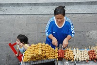 Thai woman with child Sort barbeque grill on your street