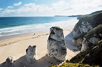 Couple walking alone on beach at the White Rocks between Portrush and Bushmills, Northern Ireland  Eroded limestone cliffs