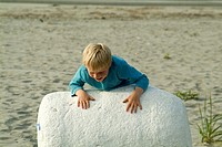 seven year old boy playing on beach, West Coast, Vancouver Island, British Columbia, Canada