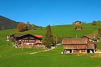 Traditional farm house in a rolling autumn landscape near Gstaad in the Bernese Oberland region, Switzerland
