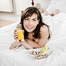 woman lying on a white bed holding orange juice