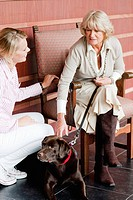 A female care assistant talking to a senior woman with a dog