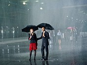 A couple standing in the rain under umbrellas