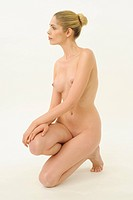 A nude woman kneeling