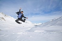 Mid adult businessman jumping in midair in mountains on winter day