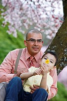 Portland, Oregon, United States Of America, A Father And His Son Sitting Under A Cherry Blossom Tree In Spring In Westmorland Park