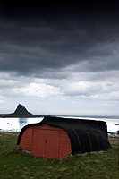 Lindisfarne, Northumberland, England, A Red Wooden Building With A View Of Lindisfarne Castle
