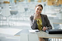 Smiling businesswoman sitting at cafeteria table