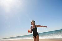 Senior woman blowing bubbles on beach
