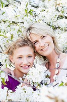 Smiling mother and daughter hugging among flowers