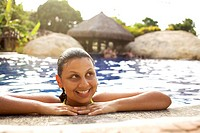 Smiling mixed race woman in swimming pool