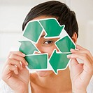 Mixed race woman holding recycling symbol in front of face (thumbnail)