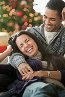 Couple cuddling and laughing on sofa
