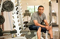 African American man resting in health club on weight_lifting bench