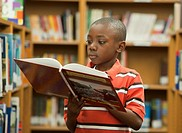 Black boy reading book in library