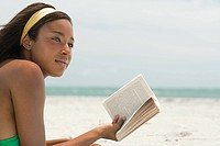 Woman at the beach with book