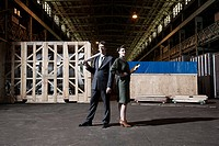 Businessman and businesswoman in warehouse