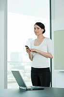 Businesswoman with mobile phone and laptop