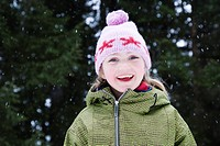 Young girl in wooly hat with snow flakes