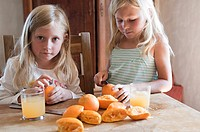 Girls making fresh orange juice