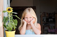 Blond girl with sunflower, portrait