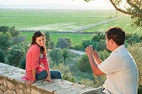 Young couple sitting on stone wall taking photograph