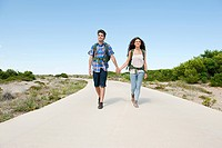 Young couple walking down rural road